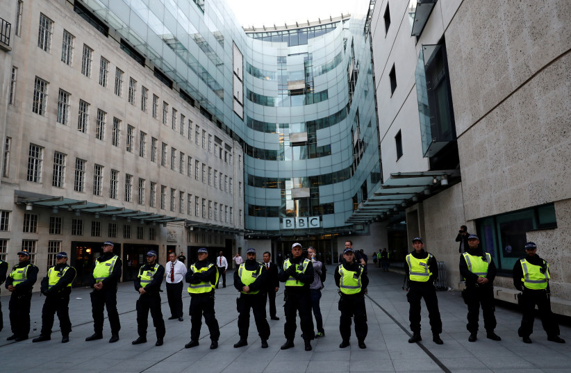 Police officers protect the entrance to the BBC building (photo credit: STEFAN WERMUTH/REUTERS)