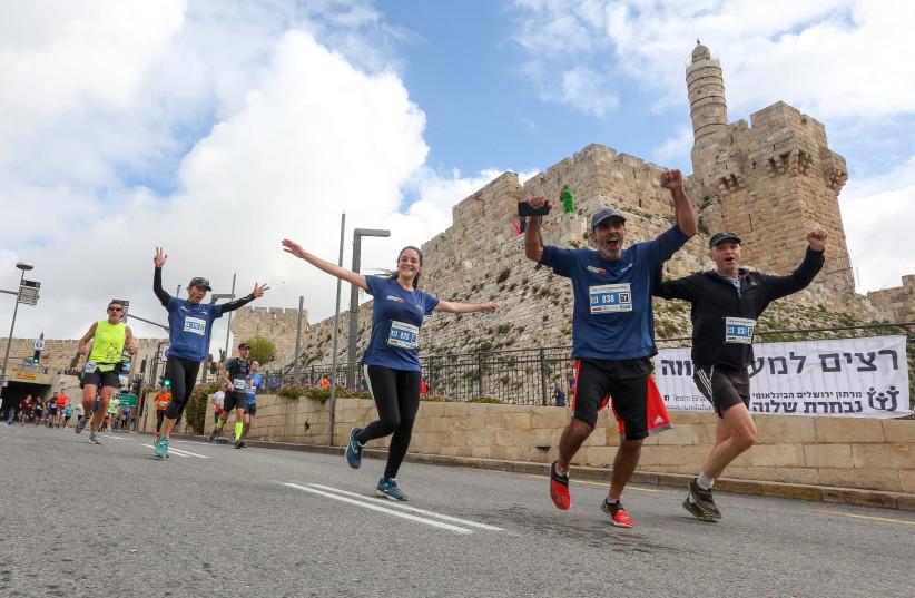 Jerusalem Marathon runners run past the Jerusalem's Old City walls, March 15th, 2019 (photo credit: MARC ISRAEL SELLEM/THE JERUSALEM POST)