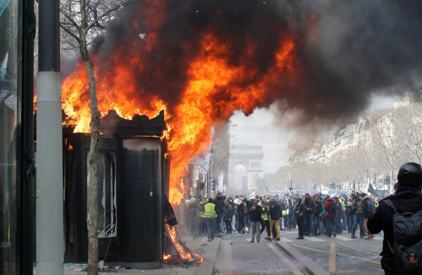 """A burning newsagent's shop is seen during a demonstration by the """"yellow vests"""" movement in Paris, France, March 16, 2019. (photo credit: PHILIPPE WOJAZER / REUTERS)"""
