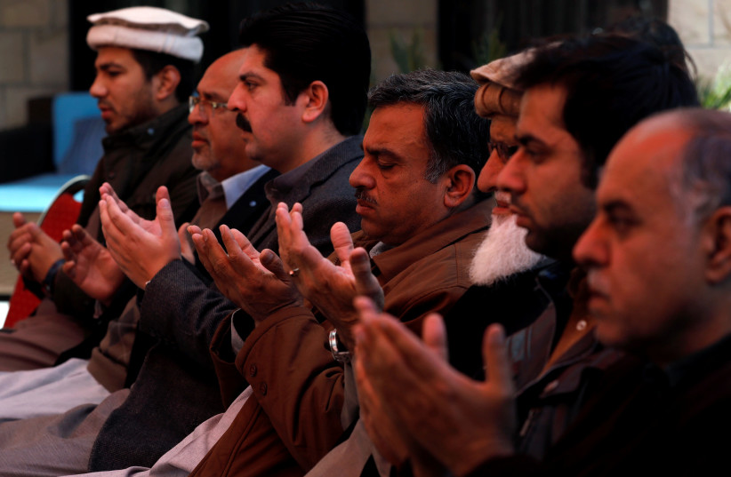 Relatives and family members of Naeem Rashid who was killed along with his son Talha Naeem in the Christchurch mosque attack in New Zealand, pray during a condolence gathering at the family's home in Abbottabad, Pakistan March 17, 2019 (photo credit: REUTERS)