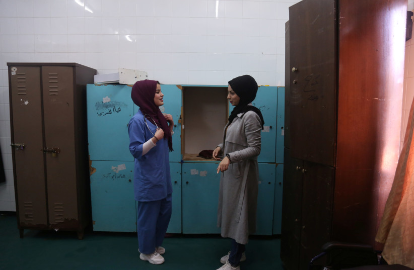 Palestinian midwife Sara Abu Taqea (L), 23, who works in the maternity ward at Gaza's Al-Ahli hospital, speaks with her colleague at the hospital in Gaza City, February 10, 2019.  (photo credit: REUTERS/SAMAR ABO ELOUF)