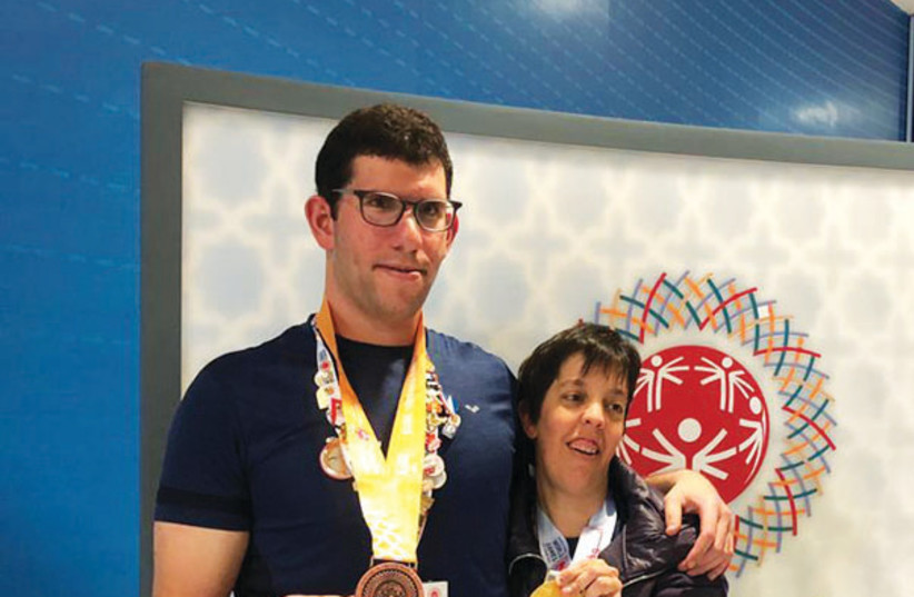 ISRAELI SWIMMERS Gilad Kalishov (left) and Avital Naveh (right) pose with the medals that they won over the weekend at the 2019 Special Olympics in Abu Dhabi (photo credit: SPECIAL OLYMPICS ISRAEL)