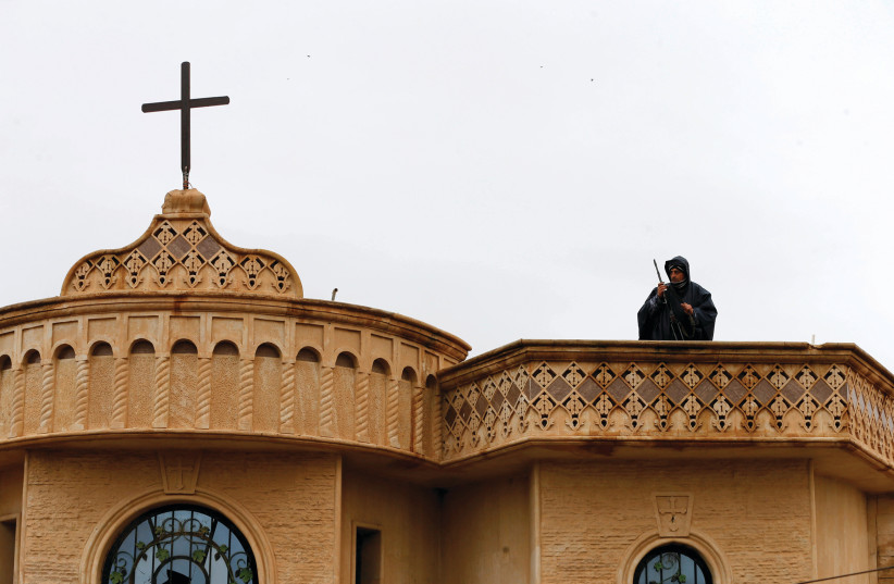 A SECURITY forces member stands atop a church in Bartella (photo credit: REUTERS)