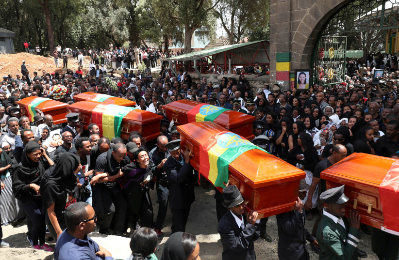 Pallbearers carry the coffins of the victims of the Ethiopian Airline Flight ET 302 plane crash, during the burial ceremony at the Holy Trinity Cathedral Orthodox church in Addis Ababa, Ethiopia, March 17, 2019.  (photo credit: REUTERS/TIKSA NEGERI)