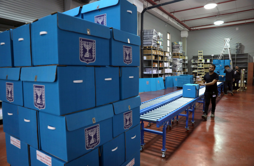 People sort ballot boxes as part of preparations for the upcoming Israeli election, during a briefing for members of the media at the Israel Central Election Committee Logistics Center in Shoham, Israel March 6, 2019 (photo credit: AMMAR AWAD/REUTERS)