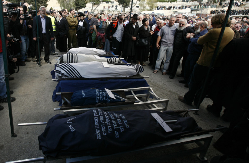 Mourners stand around the bodies of Ehud Fogel, 36, his wife Ruth, 35, and their children 11-year-old Yoav, 4-year-old Elad, and 3-month-old Hadas during their funeral in Jerusalem March 13th, 2011 (photo credit: BAZ RATNER/REUTERS)