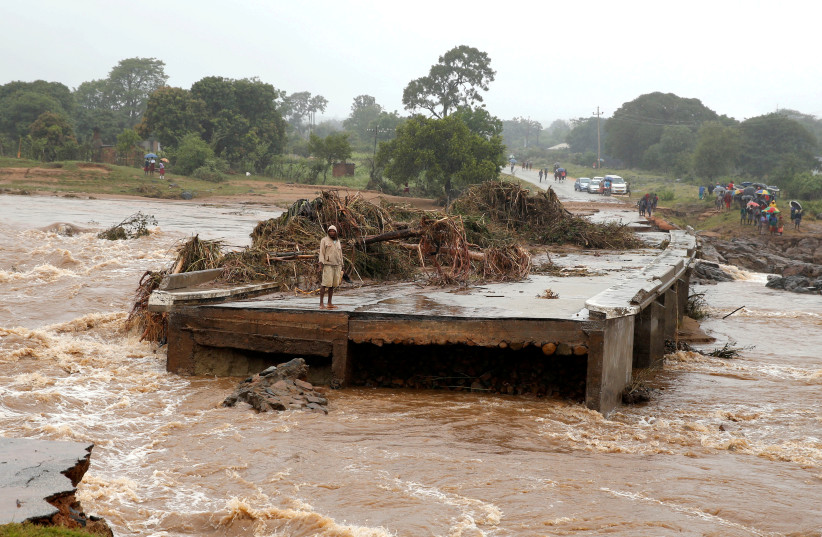 A man looks at a washed away bridge along Umvumvu river following Cyclone Ida (photo credit: PHILIMON BULAWAYO)