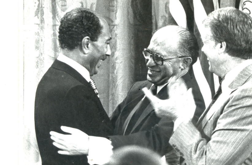 INTOXICATING DAYS: Egyptian president Anwar Sadat and prime minister Menachem Begin clasp hands with US president Jimmy Carter after the landmark 'Framework for Peace in the Middle East' was signed on the White House lawn. (photo credit: MOSHE MILNER / GPO)