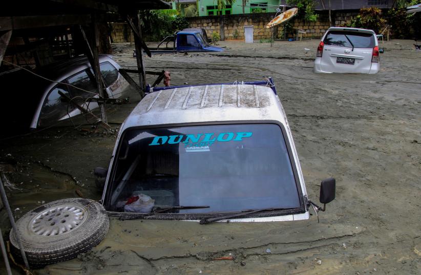 Cars are submerged in mud following a flash flood in Sentani, Papua (photo credit: ANTARA FOTO/GUSTI TANATI/ VIA REUTERS)
