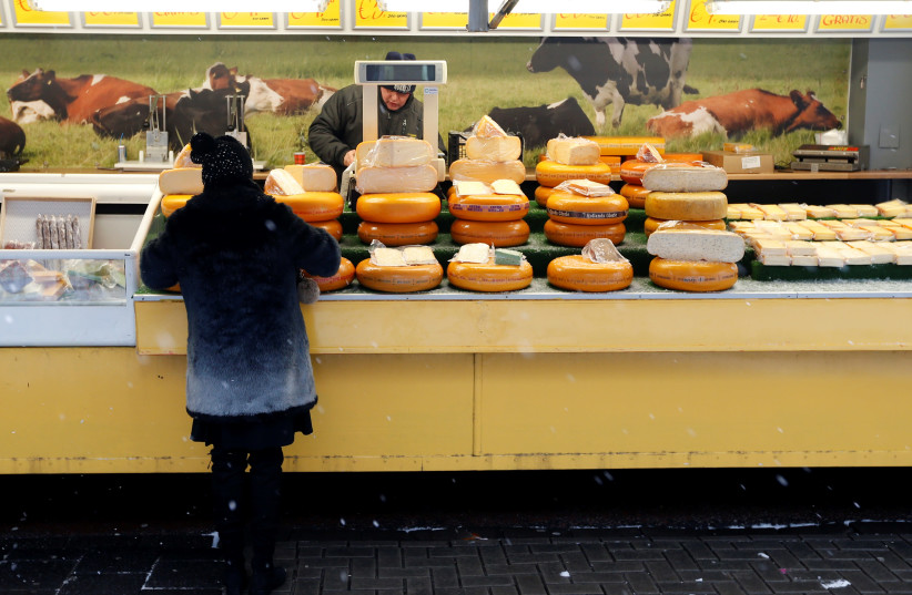 A vendor sells cheese during a weekly market in Volendam near Amsterdam (photo credit: FRANCOIS LENOIR / REUTERS)