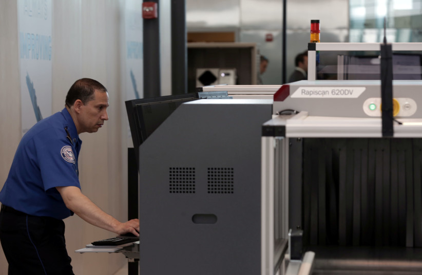 A Transport Security Administration employee scans baggage using new Automated Screening Lane technology (photo credit: JOE PENNEY)