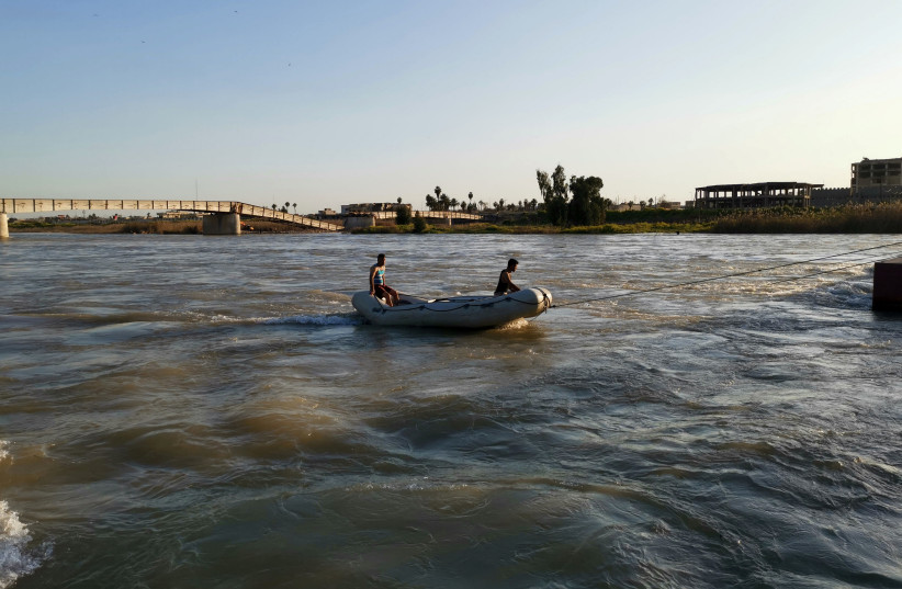 Iraqi rescuers search for survivors over the site where an overloaded ferry sank in the Tigris river (photo credit: STRINGER/ REUTERS)