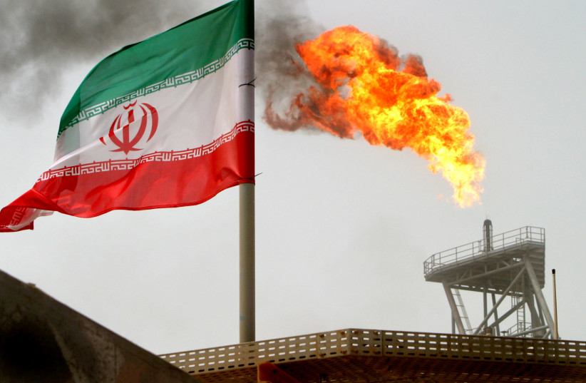 A gas flare on an oil production platform in the Soroush oil fields is seen alongside an Iranian flag in the Persian Gulf, Iran, July 25, 2005 (photo credit: RAHEB HOMAVANDI/REUTERS)