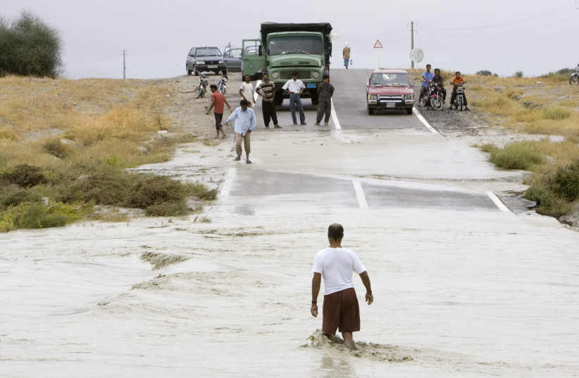 A man tries to cross a flooded road damaged by Cyclone Gonu near Jusk seaport, 2,000 km (1,240 miles) southeast of Tehran, June 8, 2007 (photo credit: REUTERS/MORTEZA NIKOUBAZL)