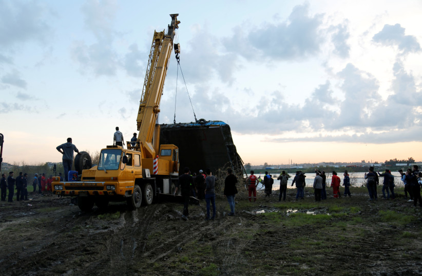 Members of the Iraqi Civil Defence rescue team lift a ferry which sank in the Tigris River with a crane in Mosul, Iraq March, 23, 2019 (photo credit: REUTERS/STRINGER)