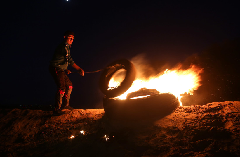 Palestinian protesters take part in a night demonstration near the fence along the border with Israel, in Rafah in the southern Gaza Strip, on March 19, 2019 (photo credit: ABED RAHIM KHATIB/NURPHOTO VIA AFP)
