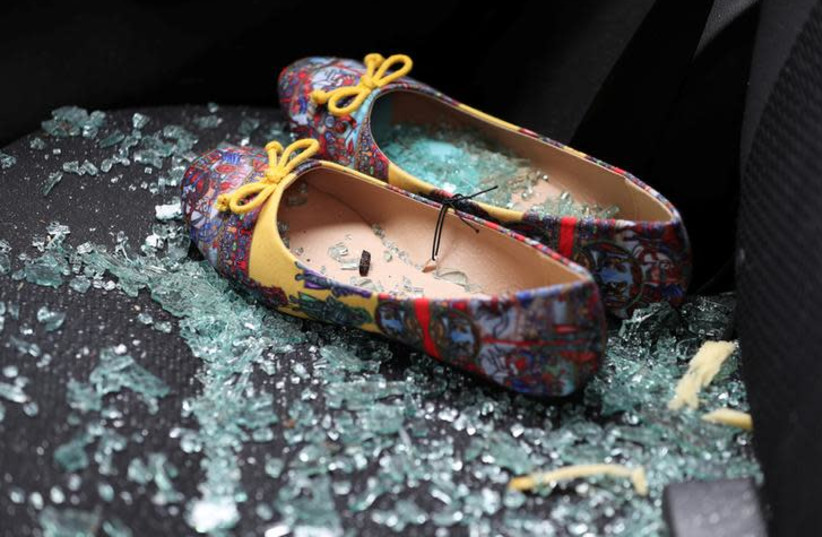 Shattered glass covers shoes left on the seat of a car that was damaged after a rocket hit a house north of Tel Aviv, Israel March 25, 2019 (photo credit: REUTERS/AMMAR AWAD)