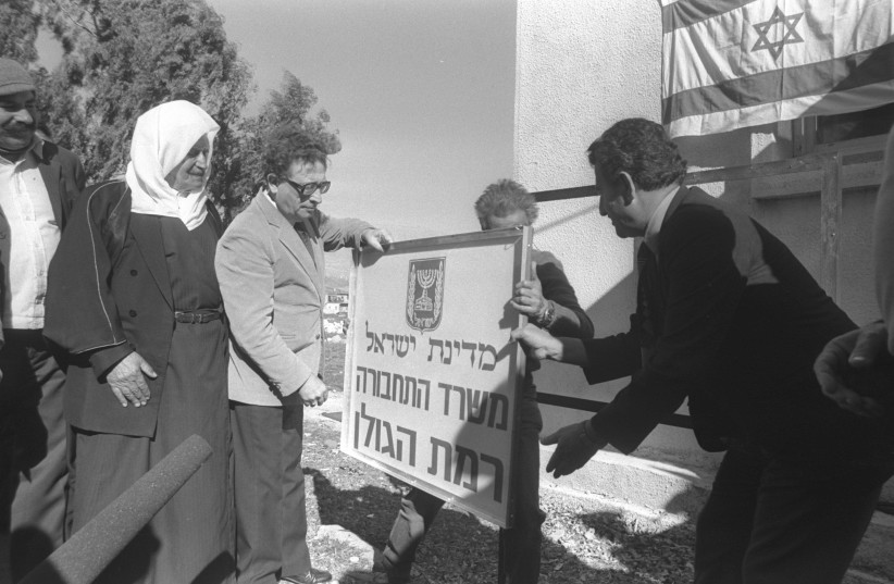 Transportation Minister Haim Corfu placing a sign  on the Golan Heights after its annexation as a Druze Israeli looks on, December 23, 1981 (photo credit: GPO ARCHIVES)