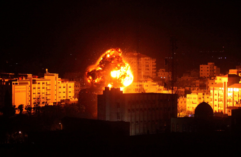 Flame and smoke are seen during an Israeli air strike in Gaza City March 25, 2019 (photo credit: MOHAMMED AJOUR/REUTERS)