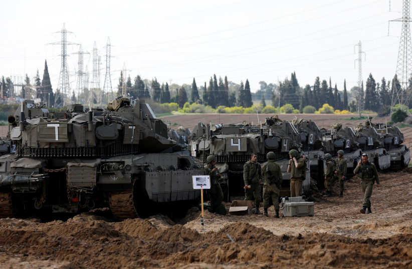 Israeli soldiers chat next to armored personnel carrier's (APC) near the border with Gaza, in southern Israel March 26, 2019 (photo credit: AMIR COHEN/REUTERS)