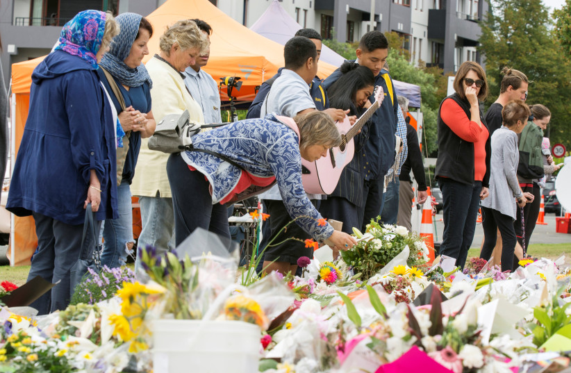 People place flowers near the police cordon for the Linwood Islamic Centre (photo credit: STRINGER/ REUTERS)