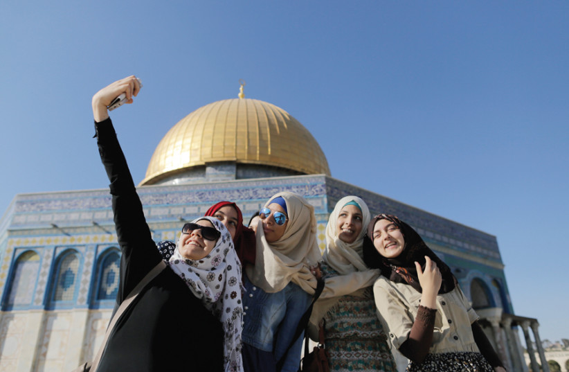 MUSLIM WOMEN pose for a selfie in front of the Dome of the Rock, Ammar Awad, 2015. (photo credit: REUTERS)