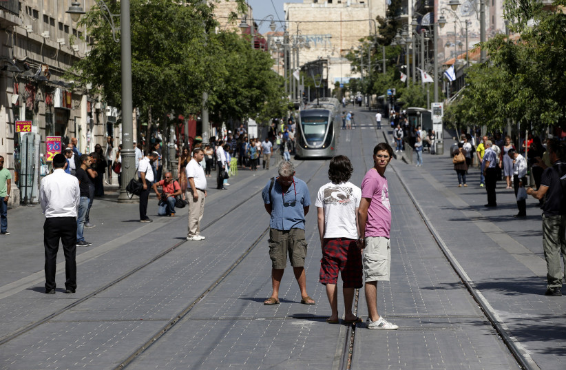 People stand still as a two-minute air raid siren is sounded marking Holocaust Remembrance Day in Jerusalem April 28, 2014 (photo credit: RONEN ZVULUN/REUTERS)