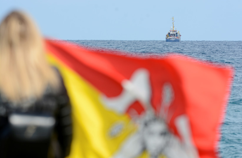 A woman holds a Sicilian flag as she looks at the migrant search and rescue ship Sea-Watch 3, operated by German NGO Sea-Watch off the coast of Siracusa, Italy, January 26, 2019.  (photo credit: GUGLIELMO MANGIAPANE / REUTERS)