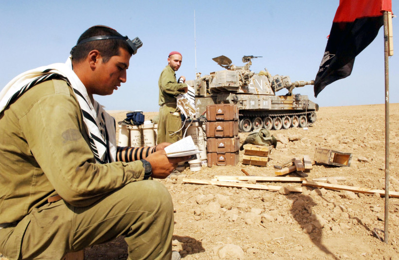 An IDF Artillery Corps soldier stationed near Gaza City partakes in morning prayers, September 26, 2015 (photo credit: MOSHE MILNER / GPO)