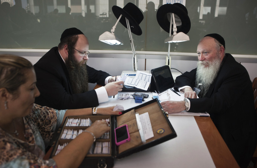 Ultra-Orthodox Jews work in the trading room of Israel's diamond exchange in Ramat Gan near Tel Aviv October 30, 2012. Diamond manufacturing is a dwindling trade in Israel. The country has one of the world's hottest diamond exchanges, but polishers and cutters of the precious stones have been replac (photo credit: NIR ELIAS / REUTERS)