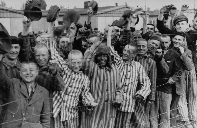 Survivors of the Nazi death camp in Dachau cheer approaching U.S. troops (photo credit: US NATIONAL ARCHIVES AND RECORDS ADMINISTRATION/WIKIMEDIA COMMONS)