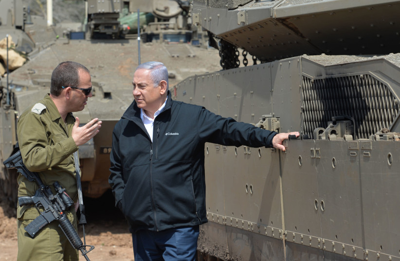 Prime Minister Benjamin Netanyahu receives a briefing from the commander of the 162nd Division during a patrol near the Gaza Strip on March 28, 2019 (photo credit: KOBI GIDEON/GPO)