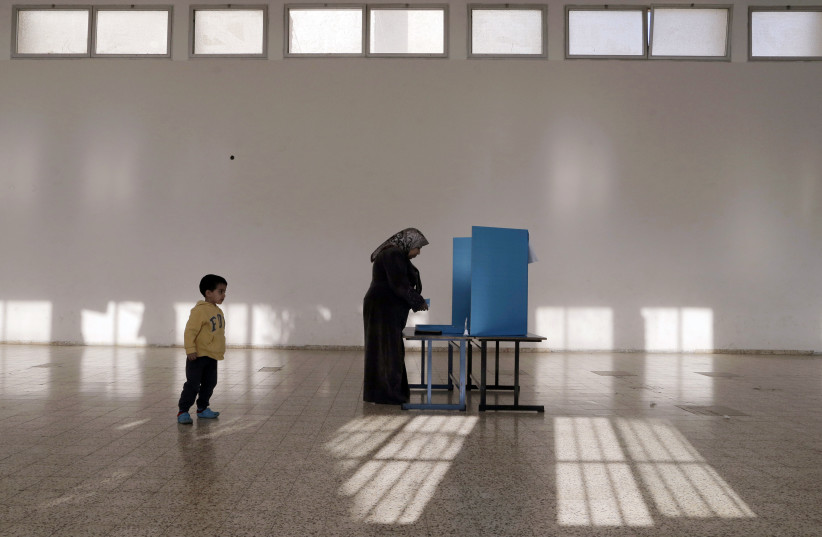 An Israeli Arab stands behind a voting booth before casting her ballot at a polling station in the northern town of Umm el-Fahm March 17, 2015 (photo credit: AMMAR AWAD/REUTERS)