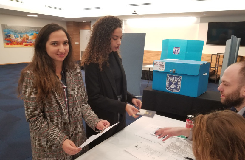 Adi Shlapok (left) and Yuval Peretz vote in the Israeli embassy in Washington, DC (photo credit: OMRI NAHMIAS)