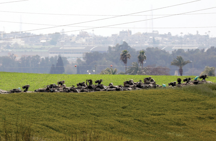 IDF ARMORED MILITARY vehicles are seen against the skyline of Gaza on Tuesday. Has a major conflict been deflected or merely delayed? (photo credit: REUTERS/AMIR COHEN)