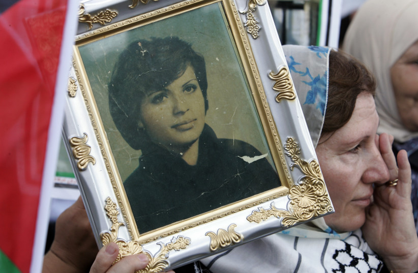 A woman holds a photo of Palestinian guerrilla Dalal al-Mughrabi as a convoy carrying her body passes by on Beirut's airport road July 17, 2008. The body of Mughrabi, who was killed while leading a 1978 raid into Israel, was handed over by Israel as part of a prisoner swap with Hezbollah. (photo credit: SHARIF KARIM / REUTERS)