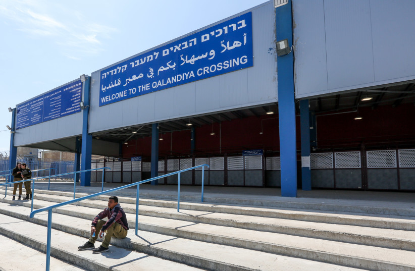 A young Palestinian sits and two IDF soldiers stand at the entrance of the Qalandiya crossing, 2019. (photo credit: MARC ISRAEL SELLEM)