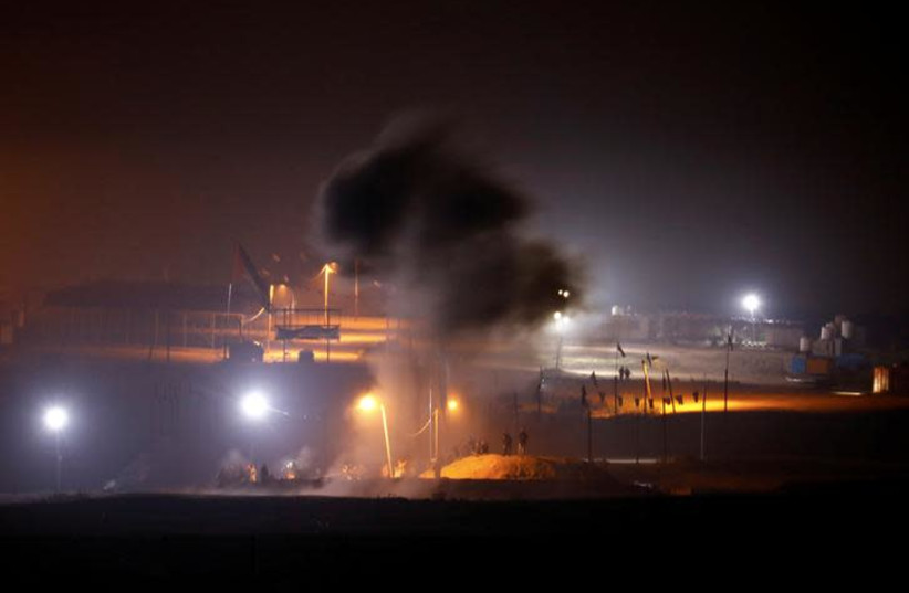 Smoke rises after an explosion as Palestinians take part in a night protest held along the Gaza side of the border with Israel (photo credit: REUTERS/AMIR COHEN)