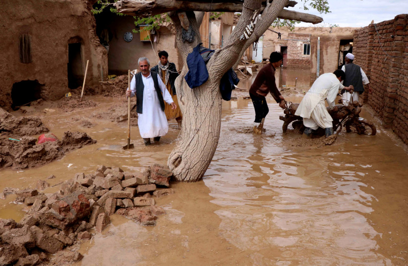 People salvage items from a house destroyed by flood in Enjil district of Herat province (photo credit: JALIL AHMAD/REUTERS)
