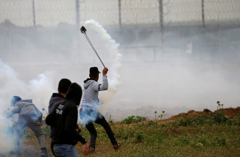 A Palestinian demonstrator uses a sling to hurl back a tear gas canister fired by Israeli forces during a protest marking Land Day and the first anniversary of a surge of border protests, at the Israel-Gaza border fence east of Gaza City March 30, 2019 (photo credit: MOHAMMED SALEM/REUTERS)