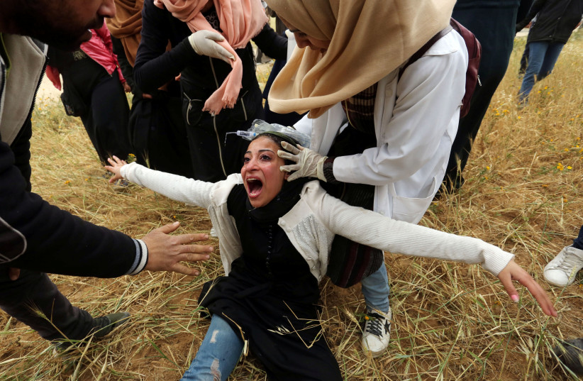 A Palestinian woman reacts after inhaling tear gas fired by Israeli forces during a protest marking Land Day and the first anniversary of a surge of border protests, at the Israel-Gaza border fence, in the southern Gaza Strip March 30, 2019.  (photo credit: ASHRAF ABU AMRAH / REUTERS)