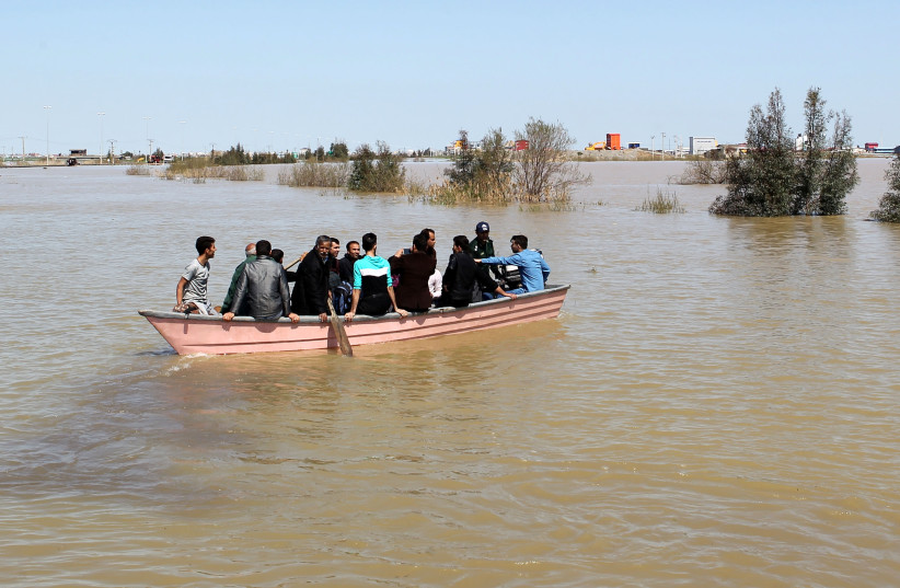 People are seen on a boat after a flooding in Golestan province, Iran, March 24, 2019. Picture taken March 24, 2019. (photo credit: TASNIM NEWS AGENCY/HANDOUT VIA REUTERS)