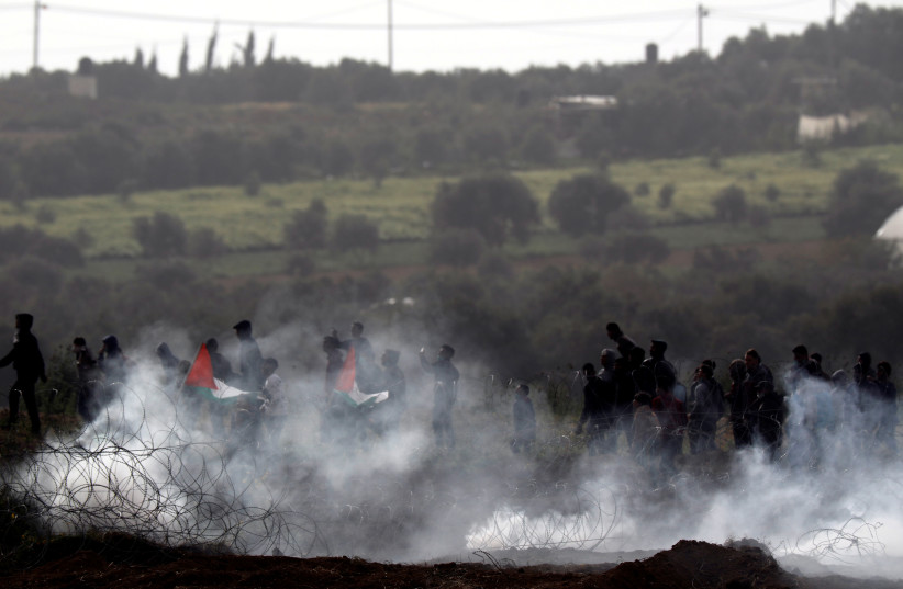 Palestinians protest next to the border fence between Israel and the Gaza Strip, as it is seen from its Israeli side March 30, 2019 (photo credit: AMIR COHEN/REUTERS)