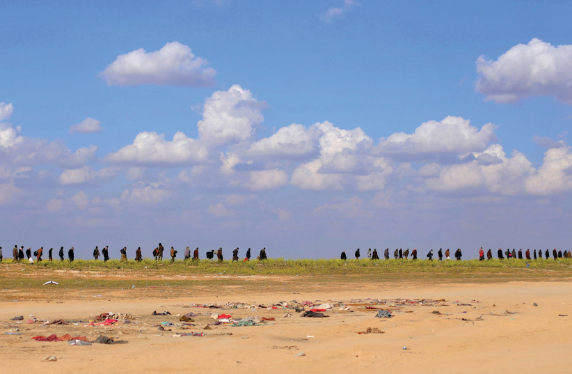 ISIS MEMBERS flee Baghouz. Now it's time to put them on trial. (Reuters) (photo credit: REUTERS)