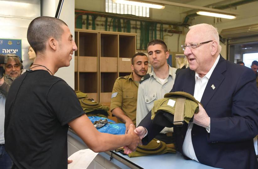 PRESIDENT REUVEN RIVLIN hands out uniforms at an IDF induction center (Mark Neyman/GPO) (photo credit: MARK NEYMAN/GPO)