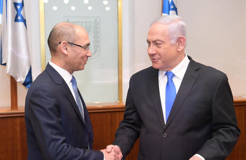 Amir Yaron (L) delivers a report to Benjamin Netanyahu (R) (photo credit: AMOS BEN-GERSHOM/GPO)
