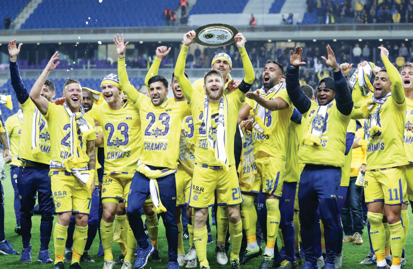MACCABI TEL AVIV players celebrate on the pitch after clinching the Israel Premier League championship on Saturday night with a 1-0 victory over Maccabi Haifa (photo credit: DANNY MAROM)