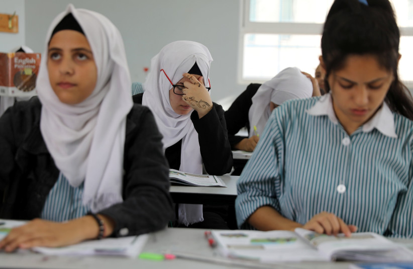 Palestinian schoolchildren take part in a lesson at a school run by UNRWA  (photo credit: AMMAR AWAD / REUTERS)