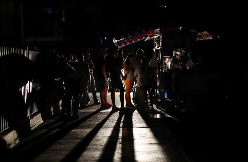 Locals gather at a street food cart during a blackout in Caracas (photo credit: IVAN ALVARADO/REUTERS)