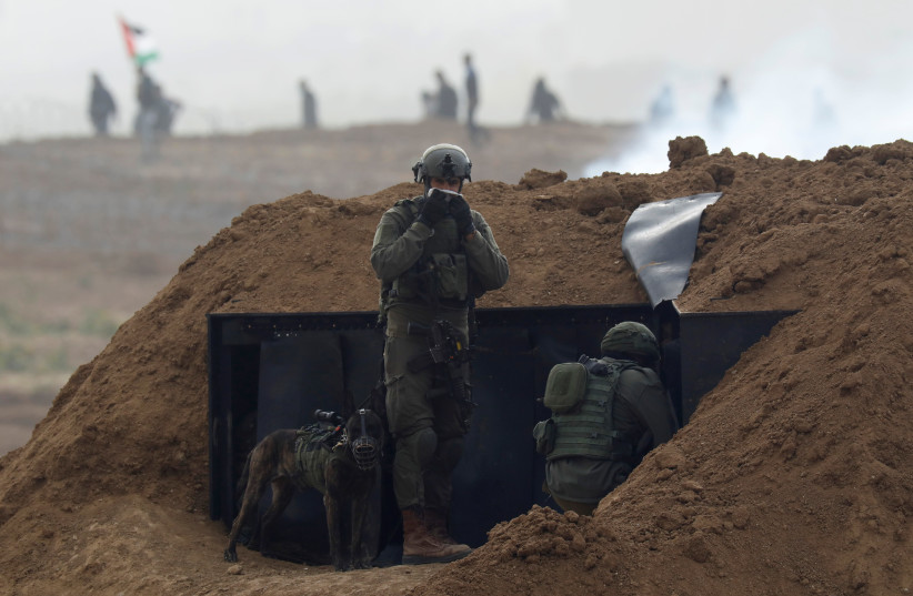 Israeli soldiers wait in position near the border fence between Israel and the Gaza Strip, during a protest on the Gaza side, as seen from the Israeli side March 30, 2019 (photo credit: REUTERS/AMIR COHEN)